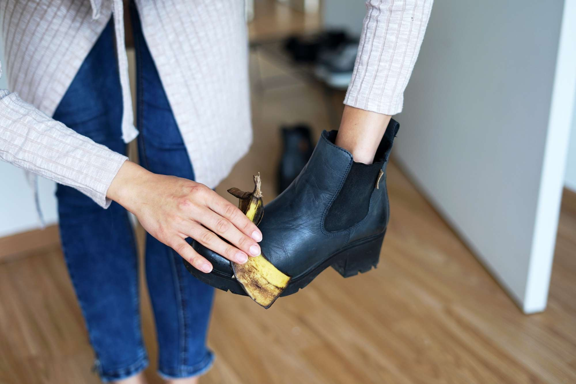 standing person rubs and polishes black leather boots down with bruised banana peel