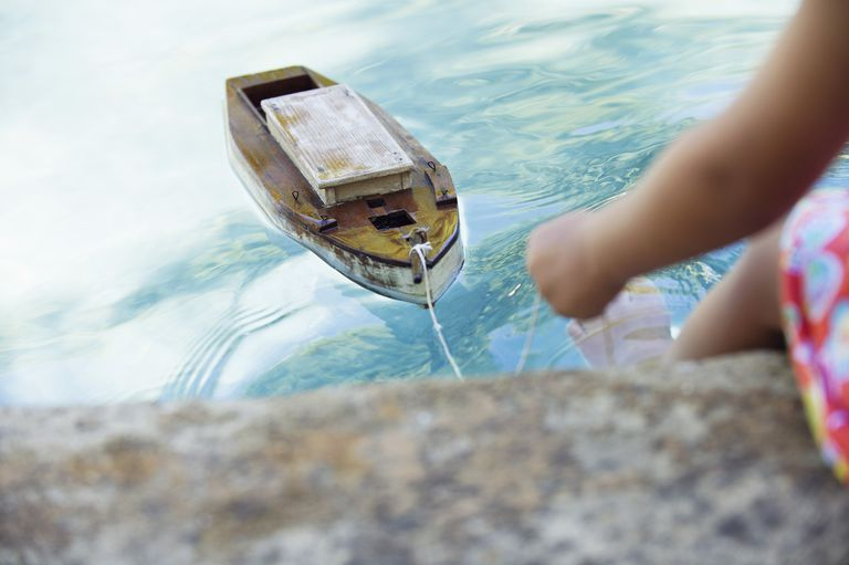Girl holding a string attached to a toy boat floating in clear water