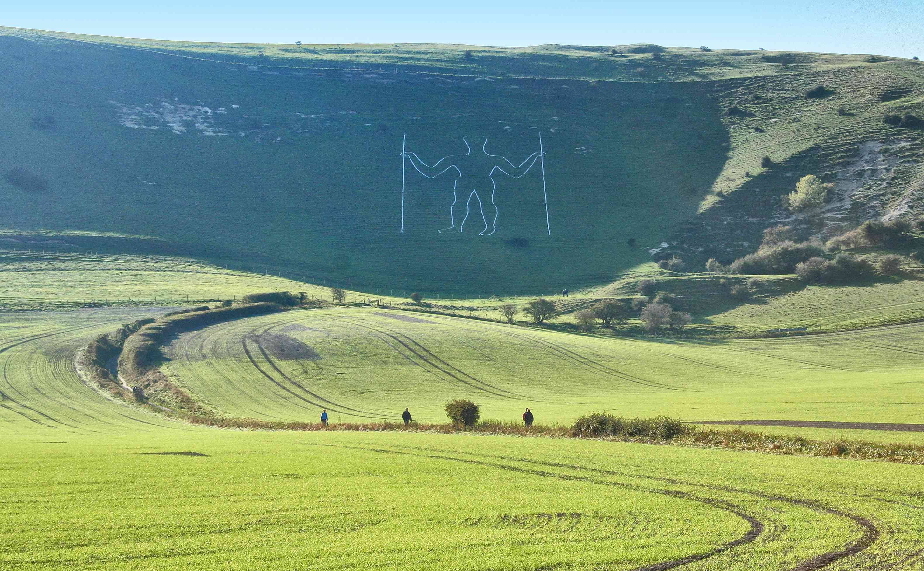 a chalk carving of Long Man of Wilmington hill carved into a steep green hill beneath a bright blue sky with rolling green hills and a few trees in the foreground