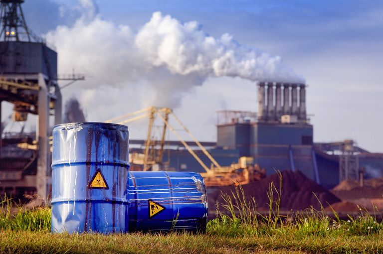 chemical waste drums in front of heavy industry