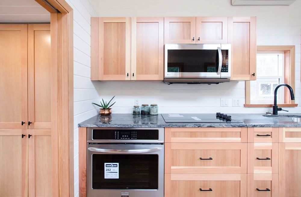 Kitchen cabinets above and below countertop, with a silver oven on the bottom