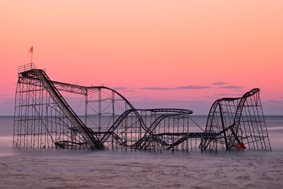 A hurricane-damaged roller coaster sits in the ocean at sunset.