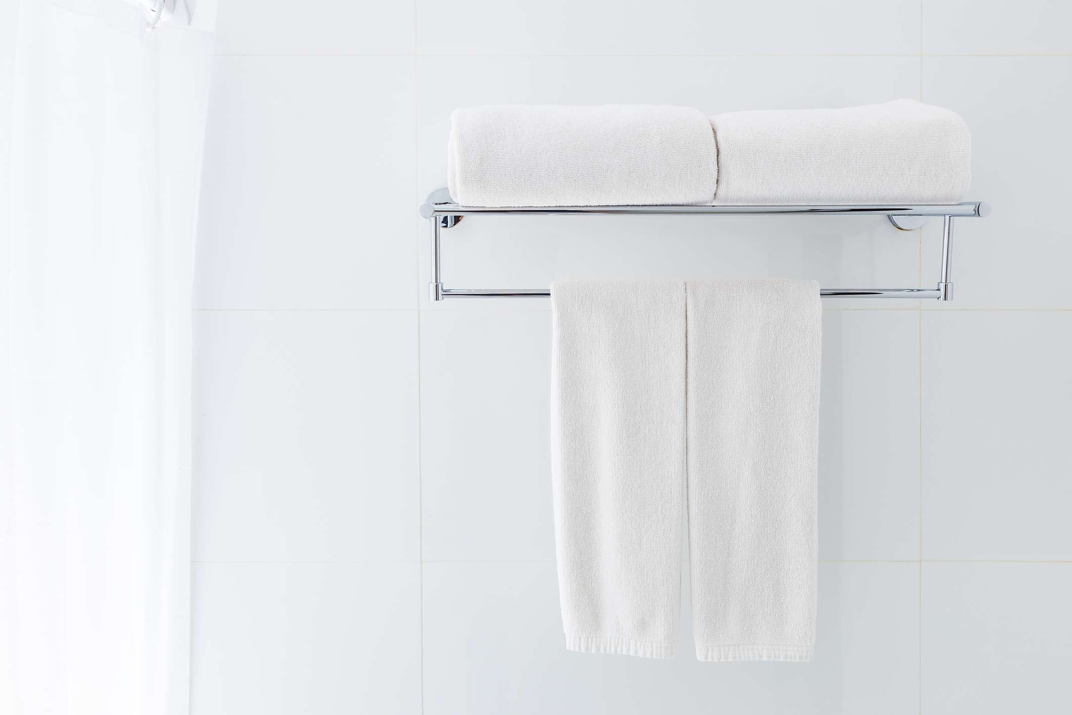 White linen towels hanging in a washroom.