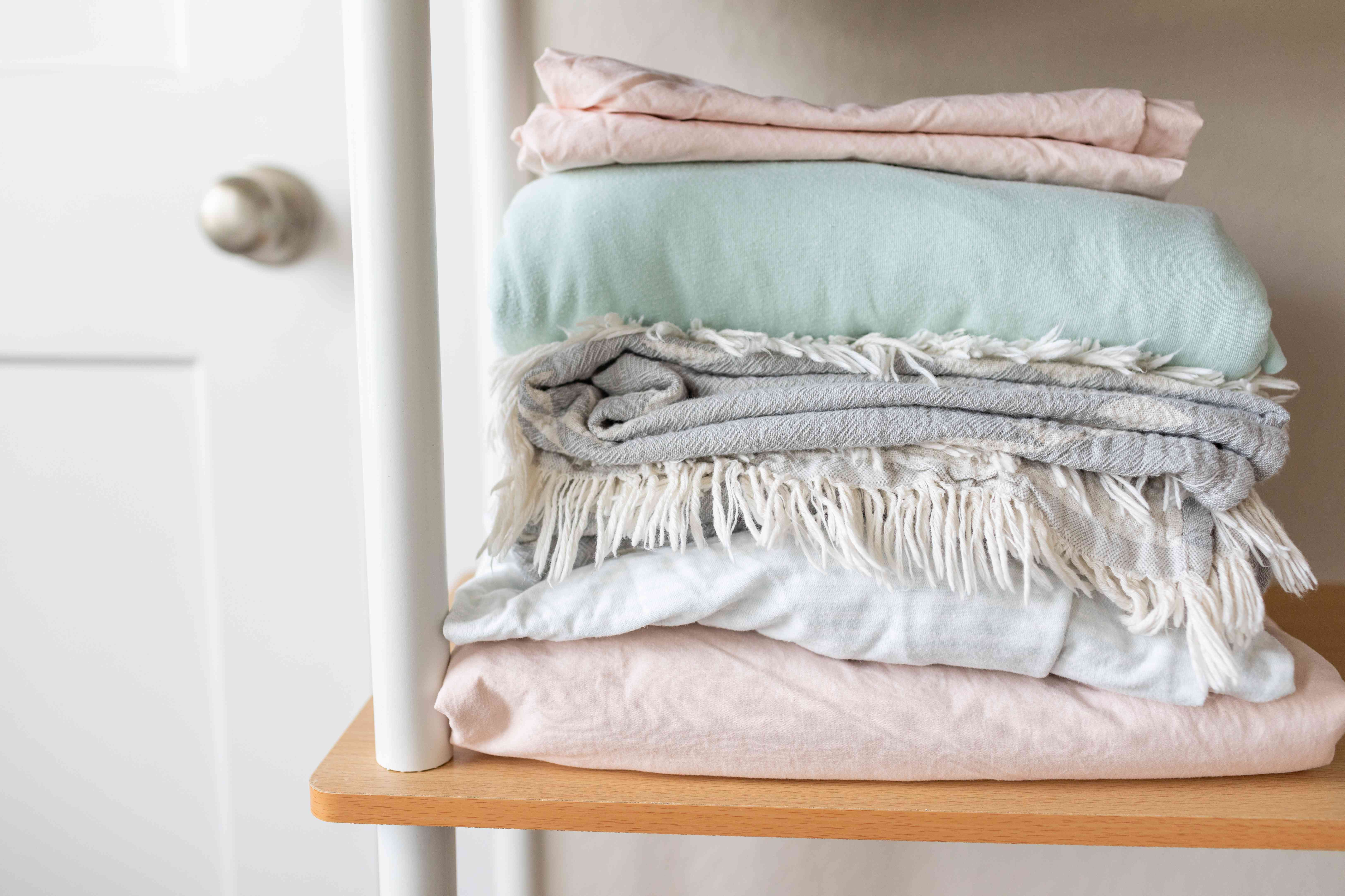 neatly folded pastel bed sheets sit on open storage rack next to white door