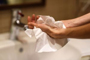 A woman dries her hand with a single paper towel.