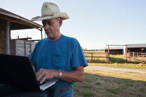Farmer using laptop by barn