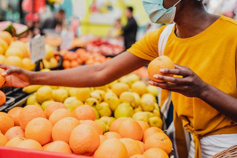 Woman choosing oranges in the produce aisle