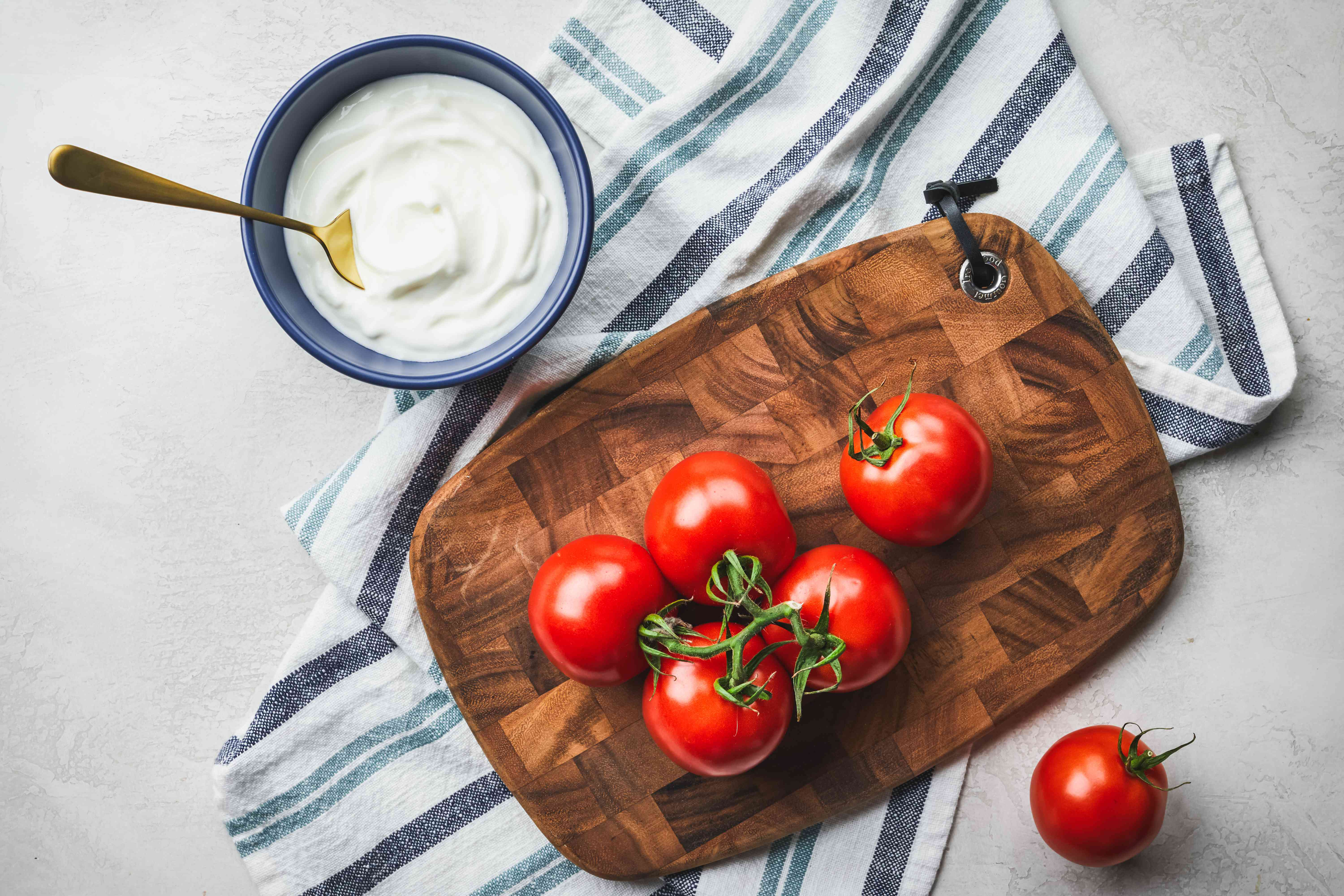 flat lay of tomatoes on vine on wooden cutting board next to bowl of greek yogurt