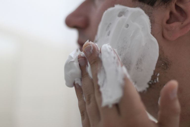 A man putting shaving cream on his face.