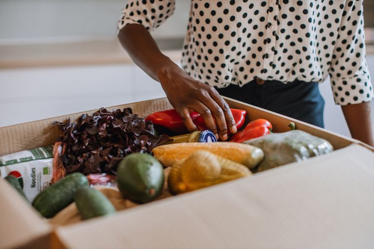 African Woman Opening Parcel With Meal Kit