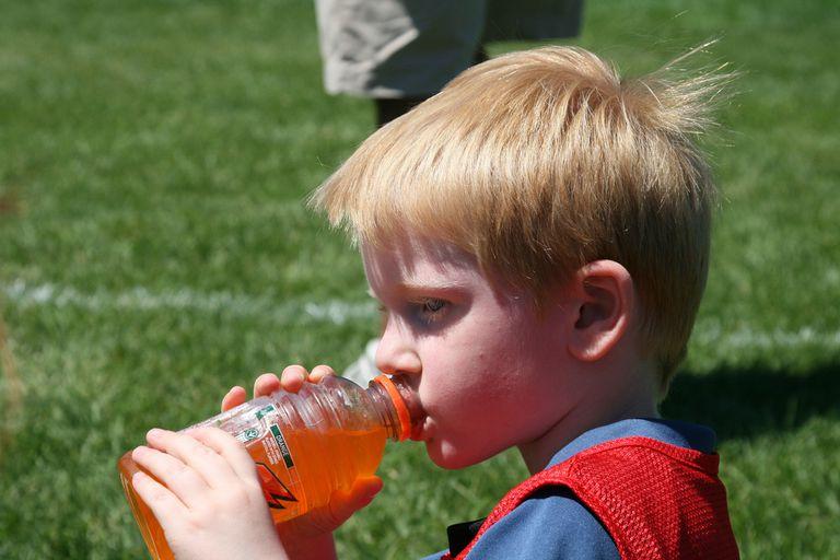 little boy drinking orange sports drink