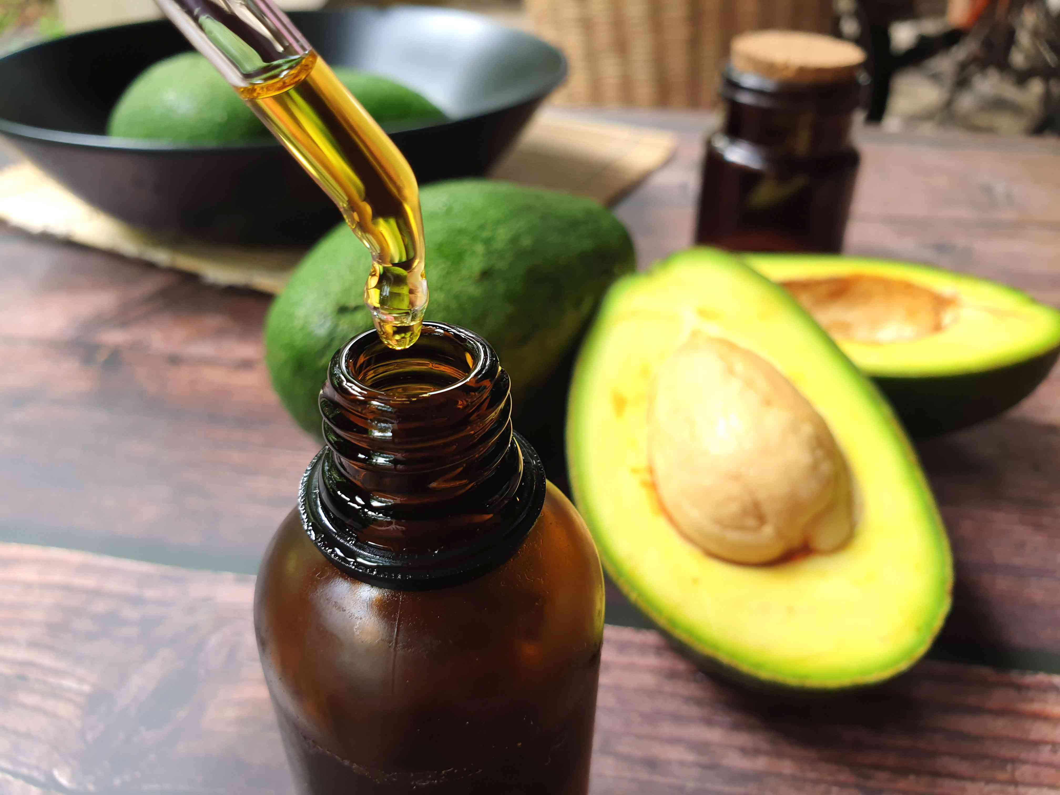 Avocados And Avocado Oil On Wooden Table