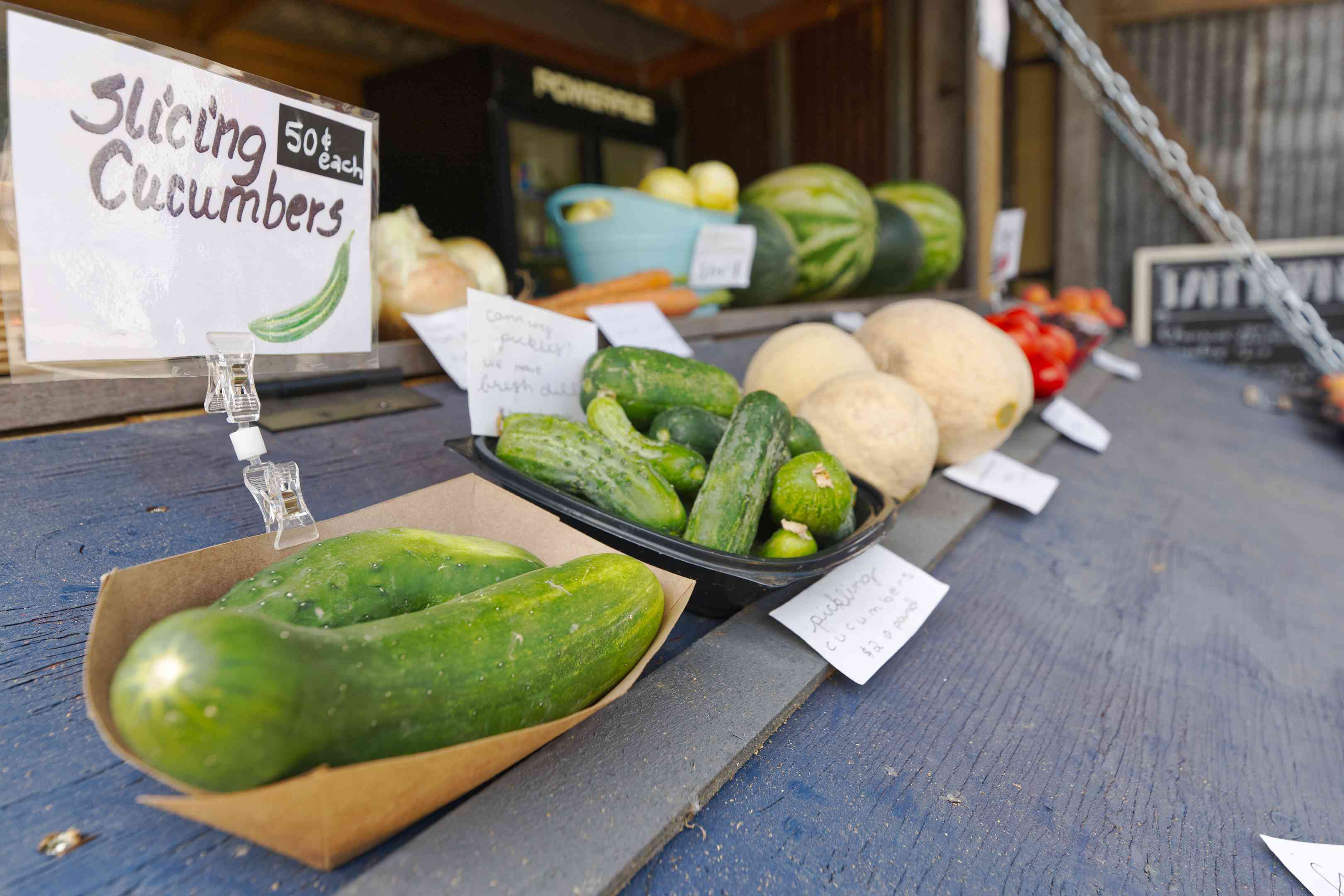 outdoor farmers market storefront with slicing cucumbers for sampling
