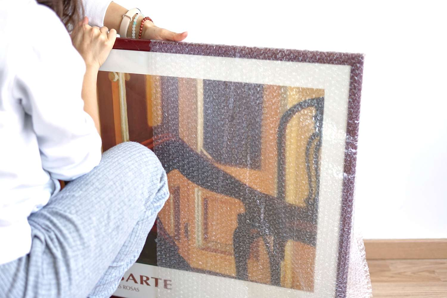 person crouches down on ground to wrap bubble wrap around framed picture for shipping