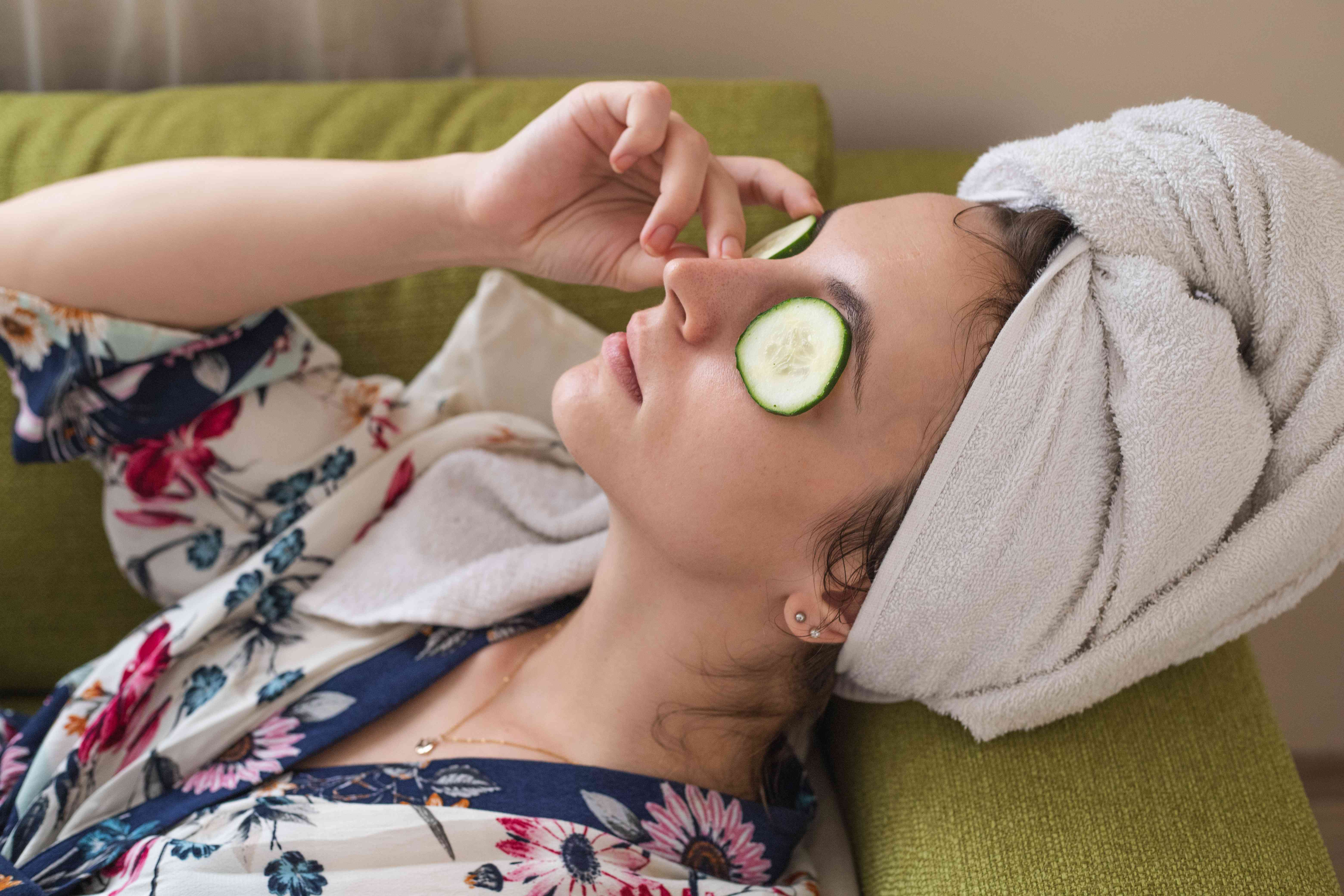 woman lies back on green couch with towel head wrap and places fresh cucumber slices on eyes