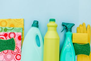 Cleaning supplies in a row, including sponges, three bottles, and a yellow rubber glove