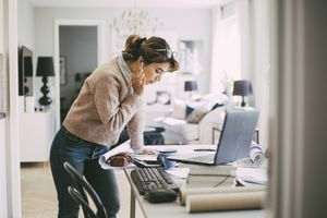 Woman standing by a table working from home