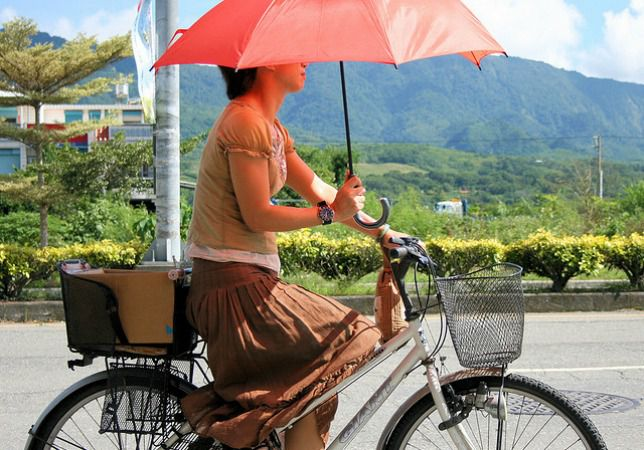 woman riding a bike while wearing a skirt and carrying a red umbrella