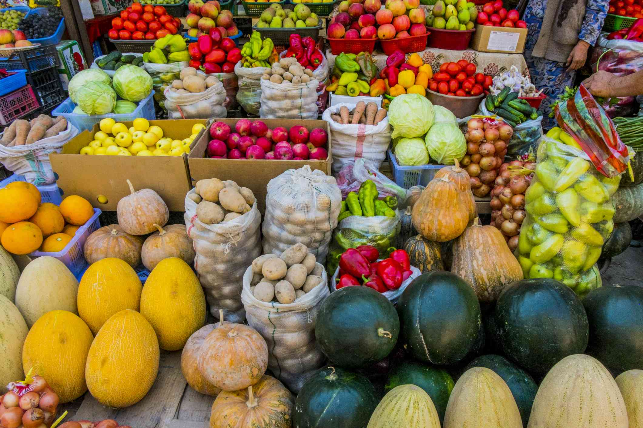 Variety of colorful fruits and vegetables, including melons, squash, tomatoes, potatoes, and apples, on tables, in boxes, and in bags at a farmer's market