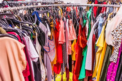Colorful garments placed tightly together on a circular rack