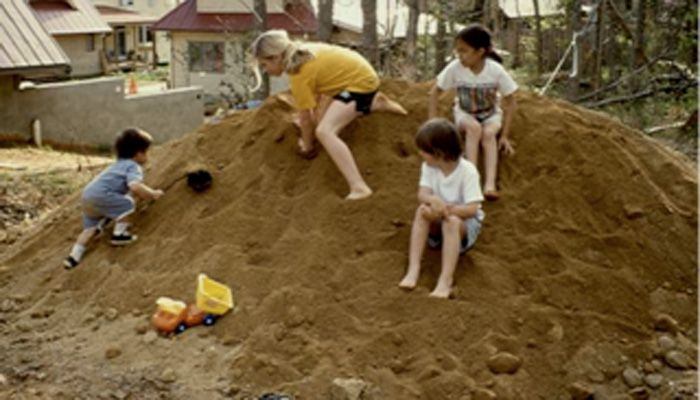 Nancy Striniste and kids play on a pile of dirt