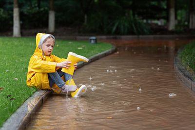 A child empties her rain boot