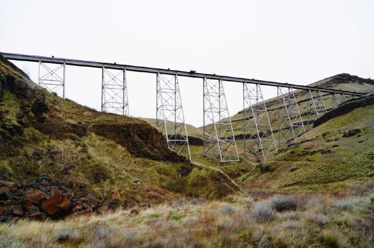 A bike trail uses a narrow bridge to pass over a dry canyon