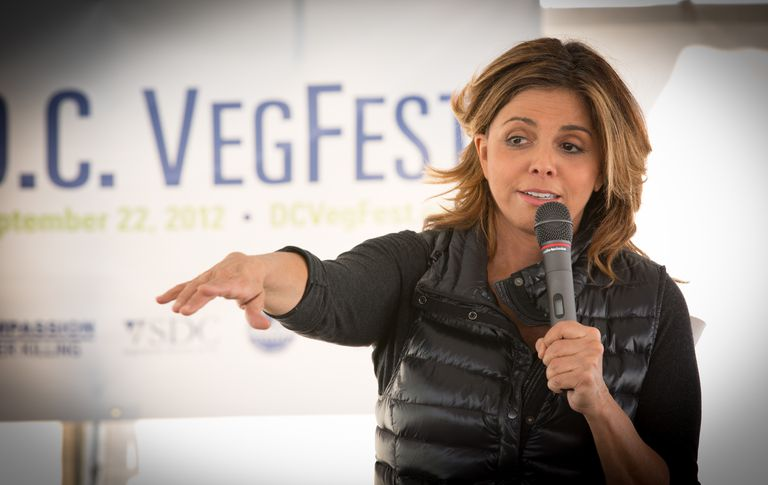A woman with brown hair and a black puffy vest speaking at veg fest.
