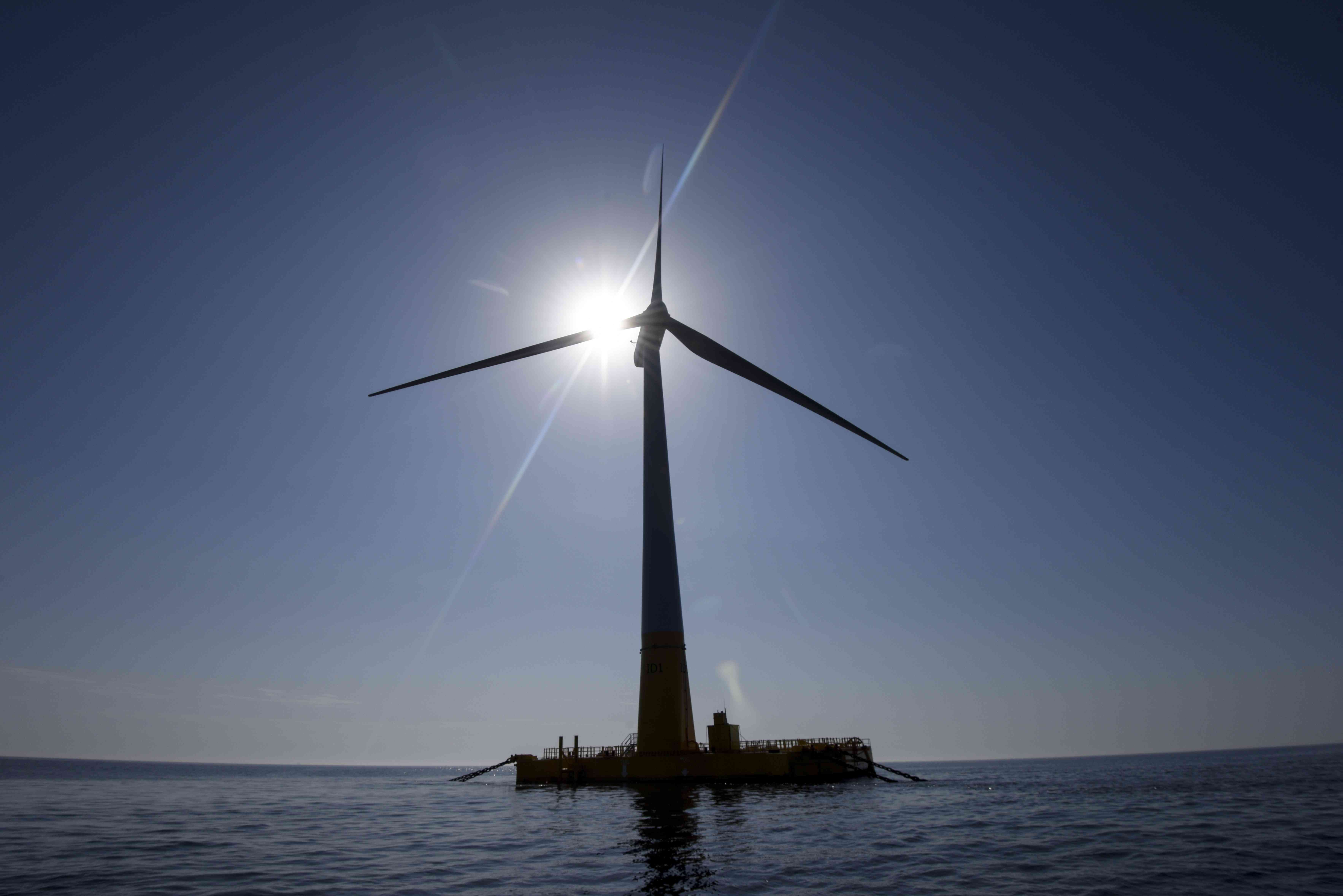 Floating wind turbine backed by the sun