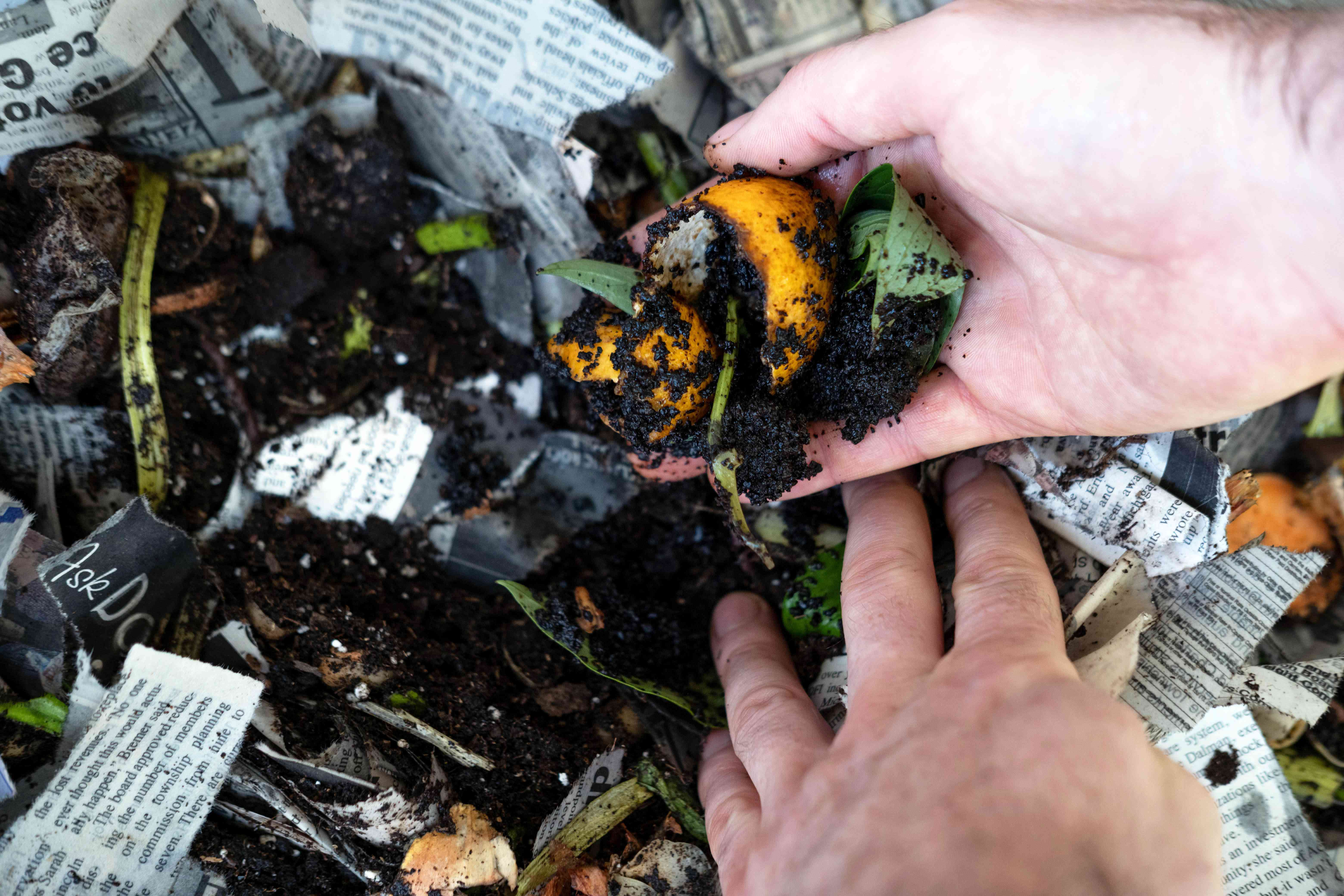 hands fluff the wet newspaper and food scraps to keep vermicomposting system fresh