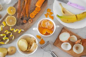 lemon, banana, carrots, and oranges peeled on a white marble kitchen counter