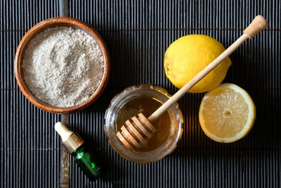 ingredients for oatmeal lemon face mask on black placemat