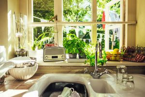 Dishes soaking in a sink under a sunny window with a radio, orchid and herbs on the windowsill