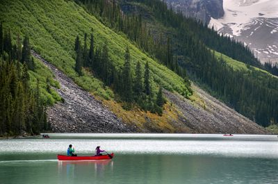 A couple in a red canoe paddle across a lake with the lower slopes of a mountain in the background