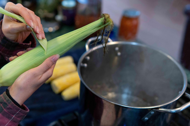 shuckin corn over boiing pot