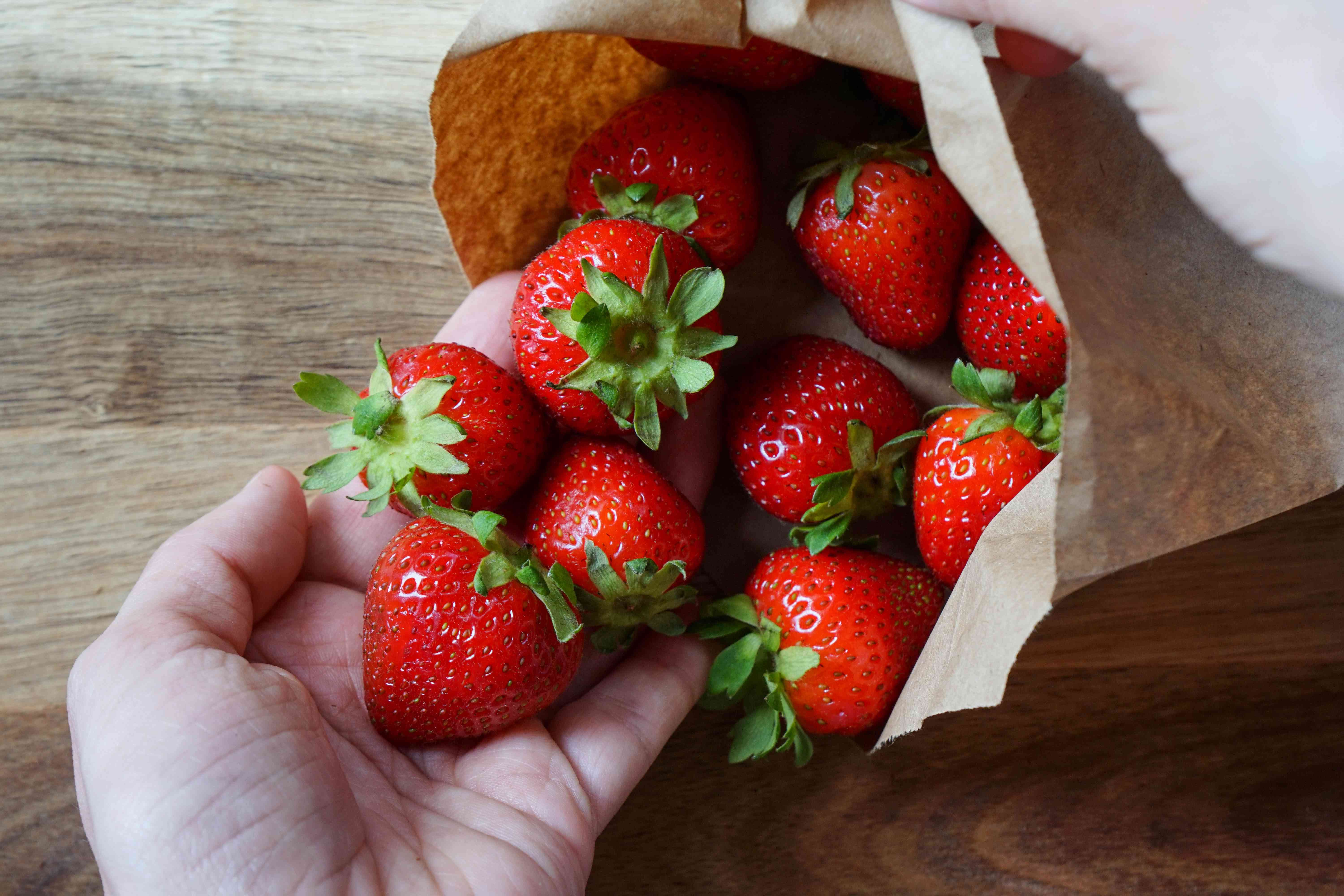 hands cradle fresh strawberries spilling out of brown paper bag