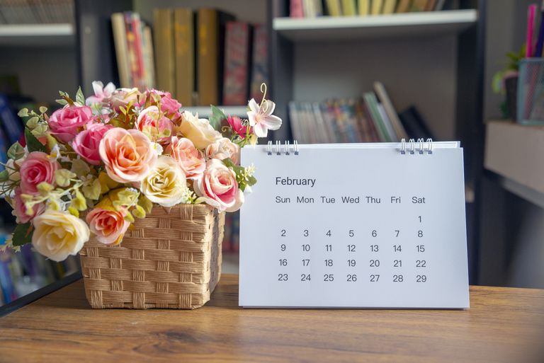 February calendar page next to a basket of flowers on a table