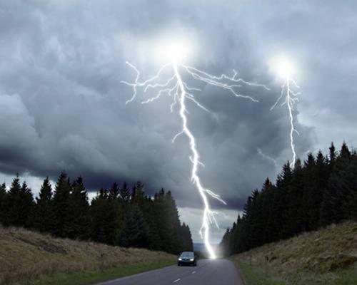 Lightning striking directly behind a moving car