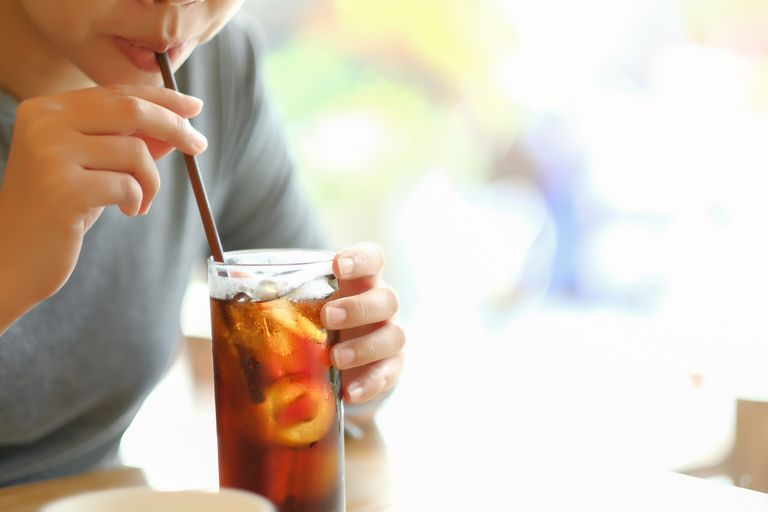 A woman drinking brown soda through a straw.