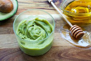 creamy DIY avocado hair mask in glass jar surrounded by spilled honey and olive oil