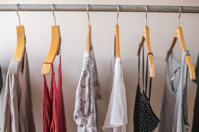 modal clothing hanging on wooden hangers on metal pole