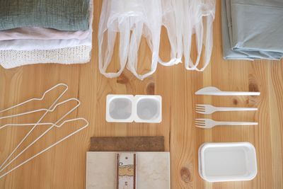 flat lay shot of textiles, plastic bags, wire hangers, and empty yogurt containers for recycling