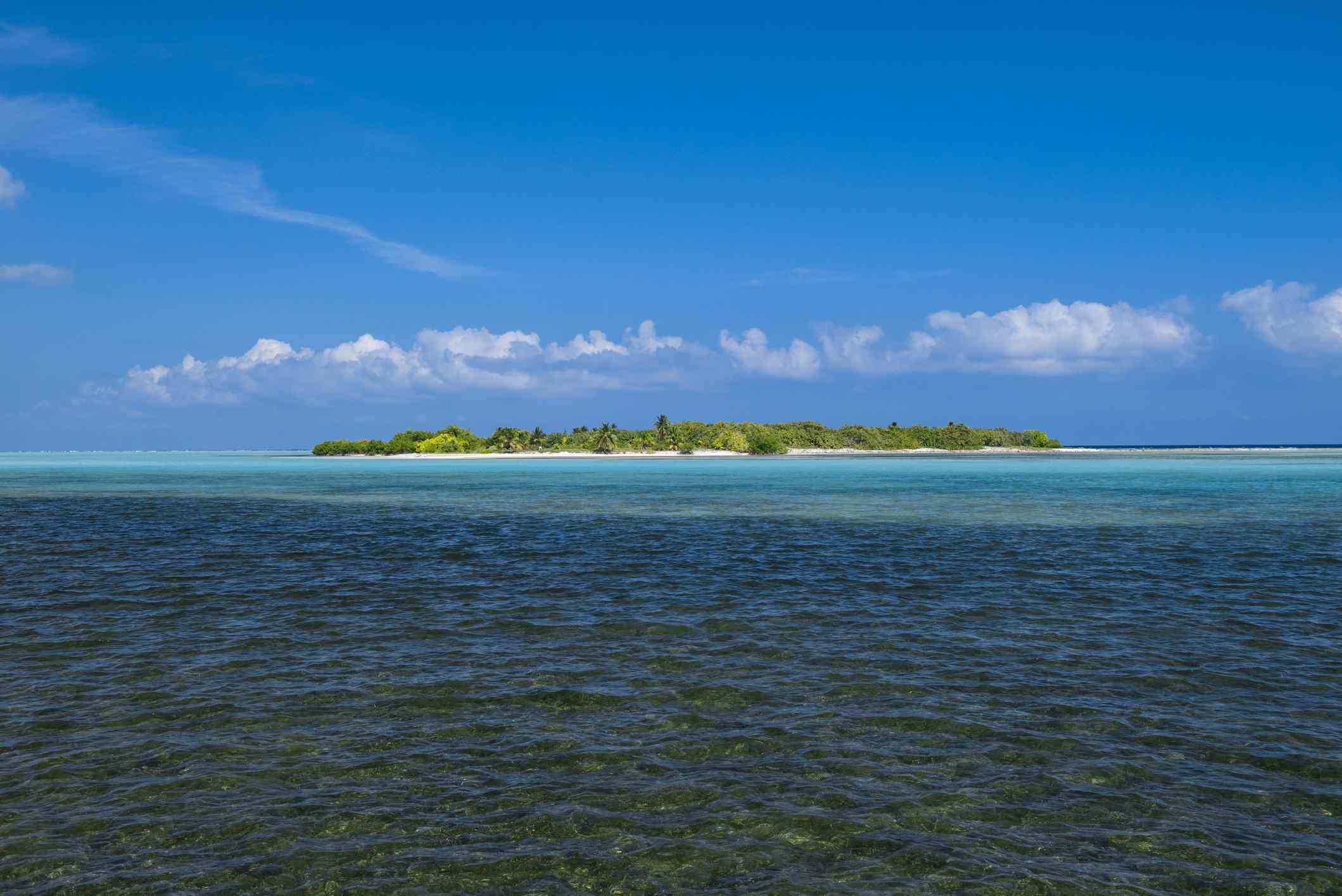 View across the ocean of Owen Island-covered in green trees and white sand-on Little Cayman Island with blue sky and low, white clouds above