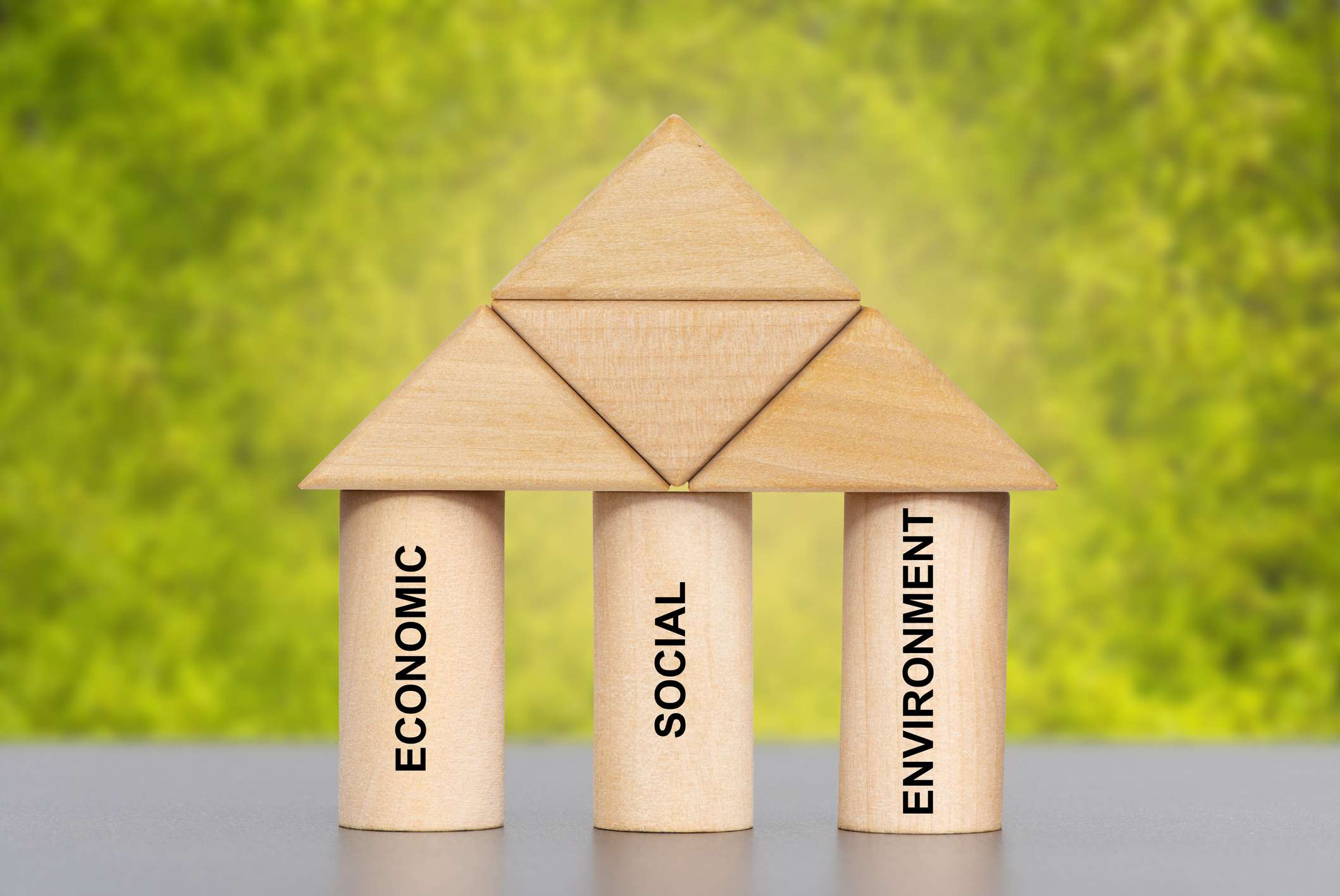 Building blocks shaped into three pillars labeled economic, social, and environment.