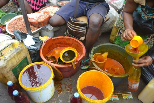 Buckets of palm oil at an outdoor market