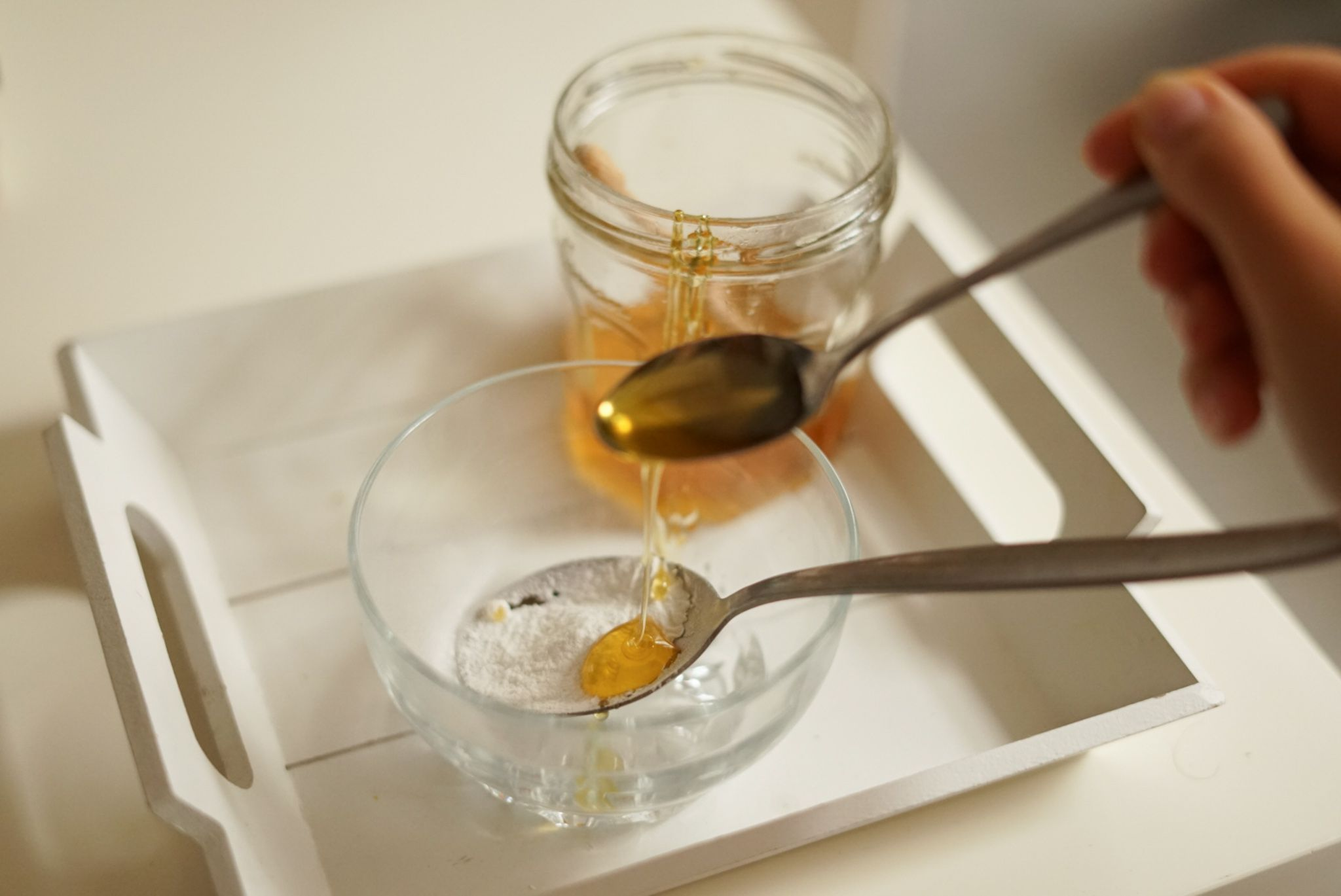 honey is drizzled from a spoon into glass jar of baking soda for natural exfoliant