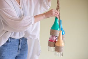 person in billowy white top holds upcycled glass bottles with twine as craft project