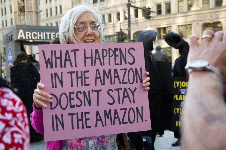 "Senior woman holding sign that says ""What happens in the Amazon doesn't stay in the Amazon"""