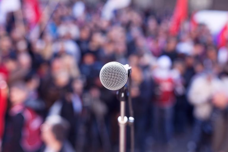 close up of microphone standing in front of gathered crowd