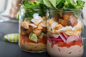 Two jars with layers of salad ingredients